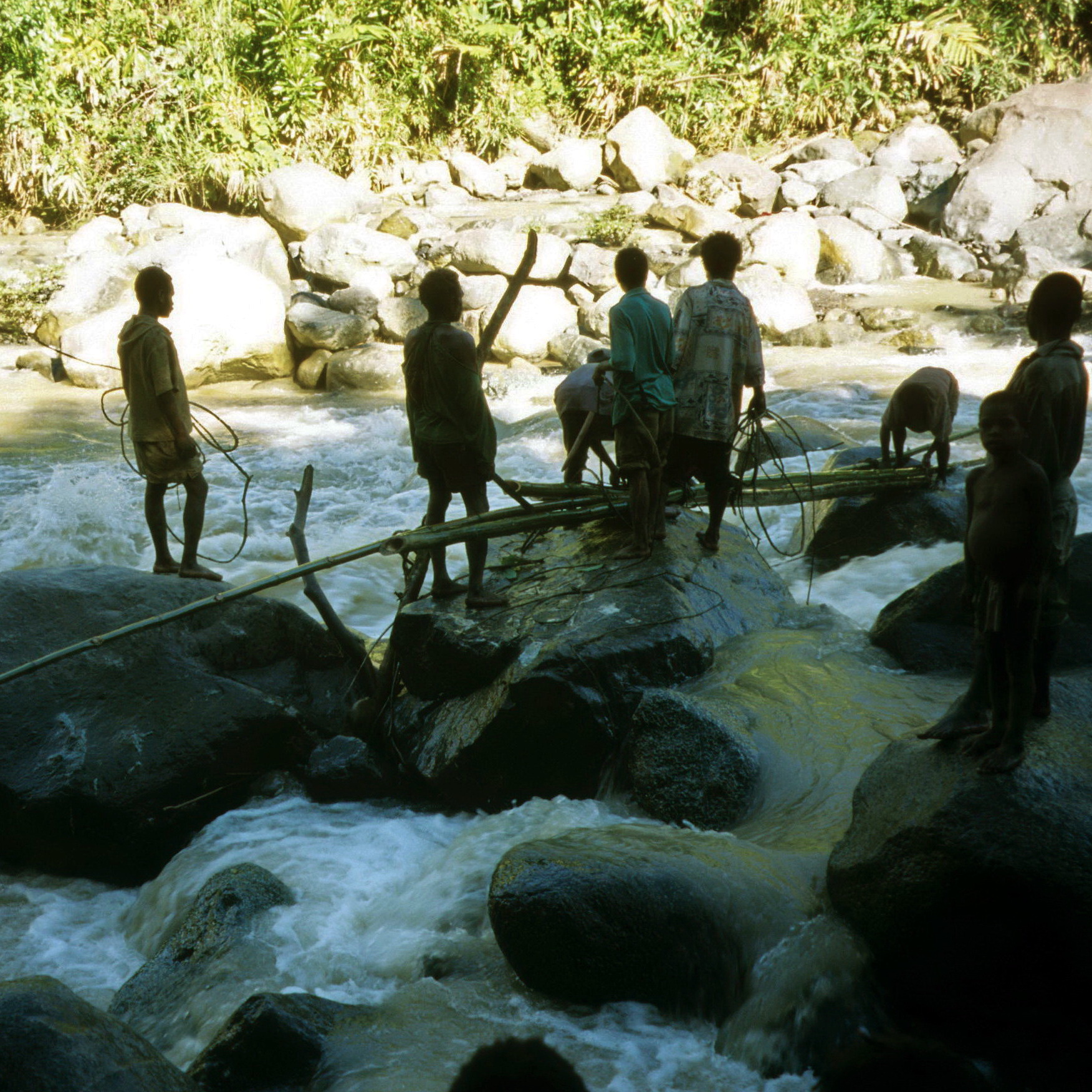 Where there is no bridge, make one.  Hiring some local guys to put up a flimsy makeshift bridge across a small river.  It looks reasonably tame in the photo but as I recall we went to all that trouble because it was too dangerous to cross on foot.
