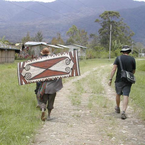 Walking through Telefomin station with nice but not ancient war shield, West Sepik Province, Papua New Guinea, circa 2004/5.